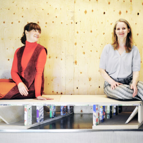 Tanja Rau og Lone Bank fra kunstnerduoen Bank & Rau med modellen af Vestbyen Stationsplads, under jernbanebroen.